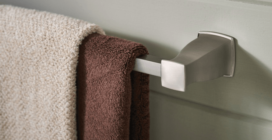 Moen hensley towel rack with cream and brown towels hanging on it